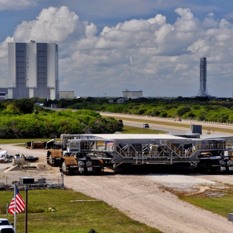 Shuttle crawler-transporter in the foreground, the Vertical Assembly building, Constellation launch tower and the Launch Control Center in the background
