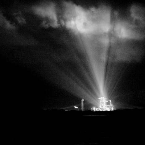 Shadows from Pad 39A play across a fast-moving, low cloud deck as xenon lights illuminate Atlantis during its final tanking ops
